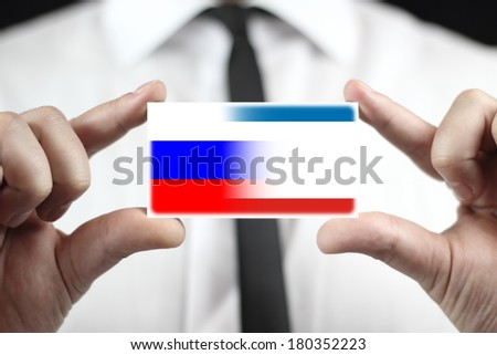 Businessman holding a business card with Autonomous Republic of Crimea and Russia Flag - stock photo