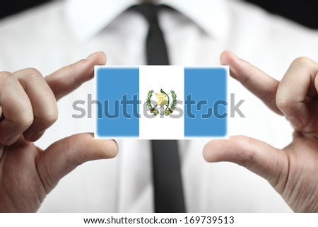 Businessman holding a business card with Guatemala Flag - stock photo