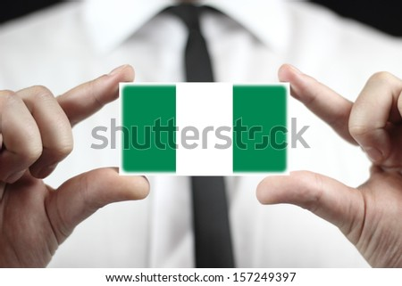 Businessman holding a business card with Nigeria Flag - stock photo