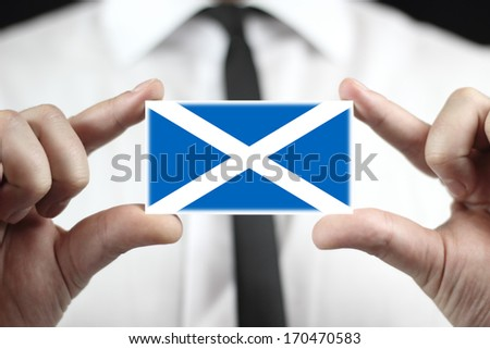 Businessman holding a business card with Scotland Flag - stock photo