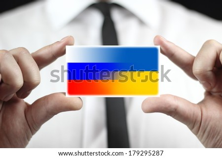 Businessman holding a business card with Ukraine and Russia Flag - stock photo