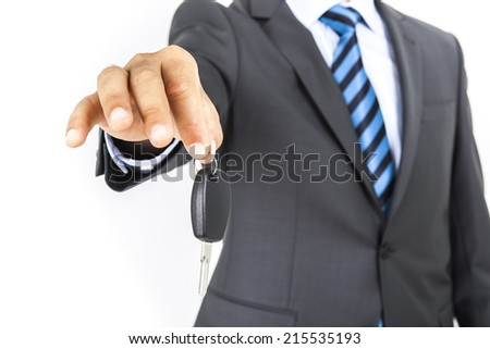 Businessman holding a car key. Isolated over white background - stock photo