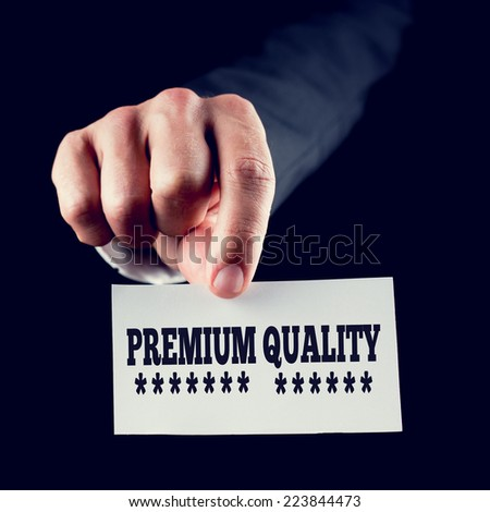 Businessman holding a card saying Premium Quality underlined with rows of stars conceptual of first-class superior quality in products and services. - stock photo