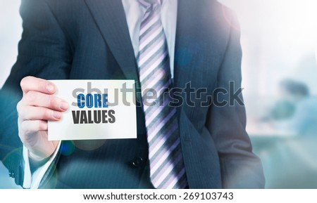 Businessman holding a card with Core Values written on it. Instagram styling applied. - stock photo