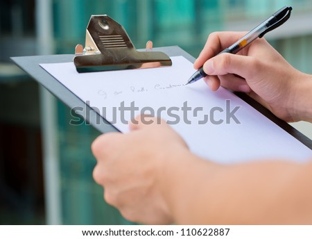 Businessman Holding A Clipboard And Writing, Out Door - stock photo