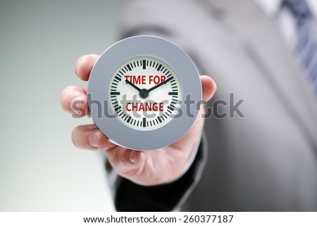 Businessman holding a clock with time for change concept for planning, improvement and progress - stock photo