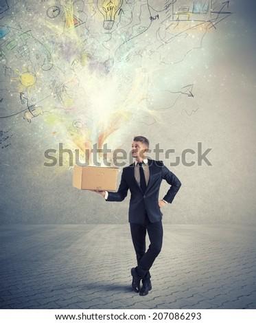 Businessman holding a creative business box - stock photo