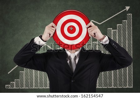 Businessman holding a dartboard on growth graph chalkboard - stock photo
