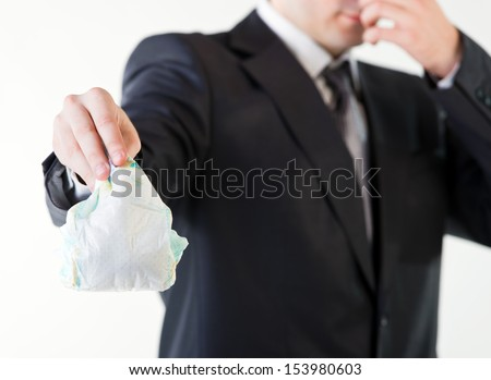 Businessman holding a dirty diaper - stock photo