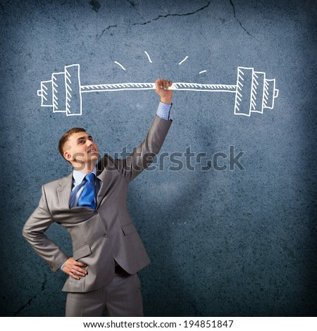 businessman holding a hand sketched barbell, concept achievements in business - stock photo