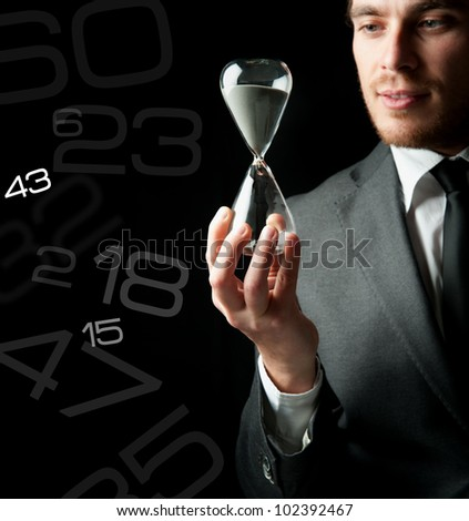 Businessman holding a hourglass with a girl inside - stock photo