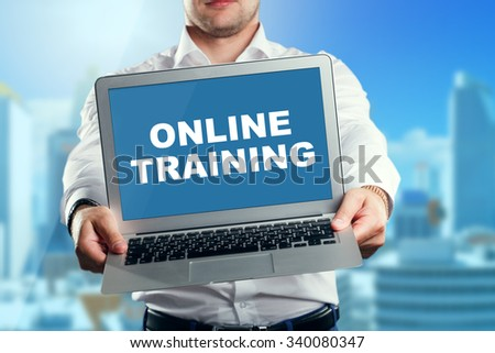 Businessman holding a laptop with an online training. Business, technology, internet and networking concept. - stock photo