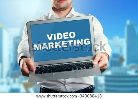 Businessman holding a laptop with an video marketing. Business, technology, internet and networking concept. - stock photo