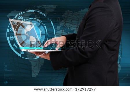 Businessman holding a laptop with globe and icon application on virtual screen. Concept of online business. - stock photo