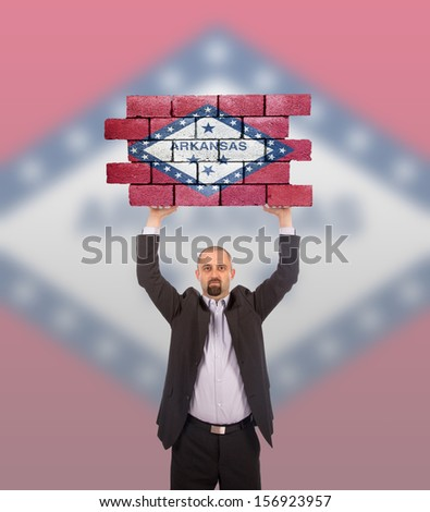 Businessman holding a large piece of a brick wall, flag of Arkansas, isolated on national flag - stock photo