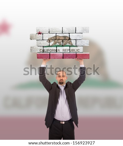 Businessman holding a large piece of a brick wall, flag of California, isolated on national flag - stock photo