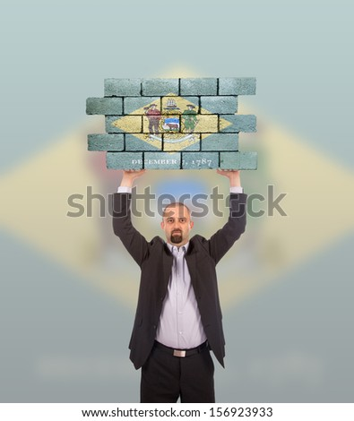 Businessman holding a large piece of a brick wall, flag of Delaware, isolated on national flag - stock photo