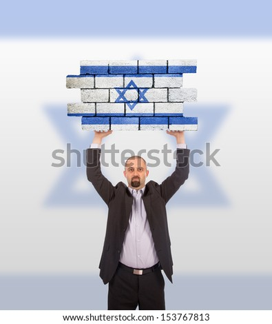 Businessman holding a large piece of a brick wall, flag of Israel, isolated on national flag - stock photo