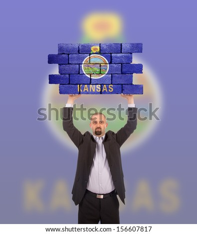 Businessman holding a large piece of a brick wall, flag of Kansas, isolated on national flag - stock photo
