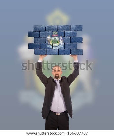 Businessman holding a large piece of a brick wall, flag of Maine, isolated on national flag - stock photo