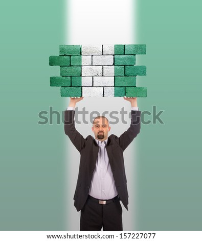 Businessman holding a large piece of a brick wall, flag of Nigeria, isolated on national flag - stock photo