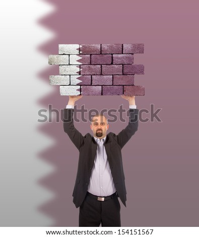 Businessman holding a large piece of a brick wall, flag of Qatar, isolated on national flag - stock photo