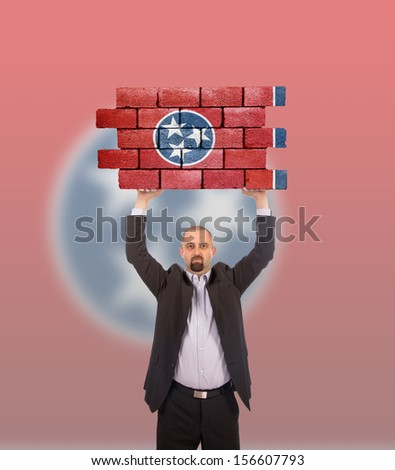 Businessman holding a large piece of a brick wall, flag of Tennessee, isolated on national flag - stock photo
