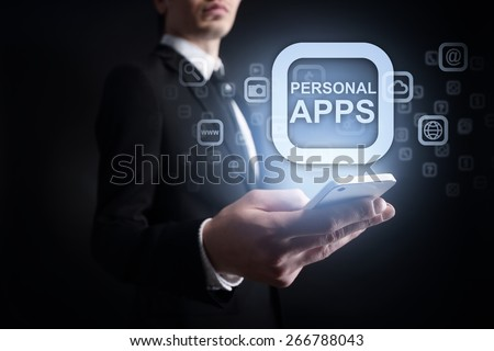 Businessman holding a mobile phone with app icon and text Personal apps on virtual screen. Internet concept. Business concept. - stock photo