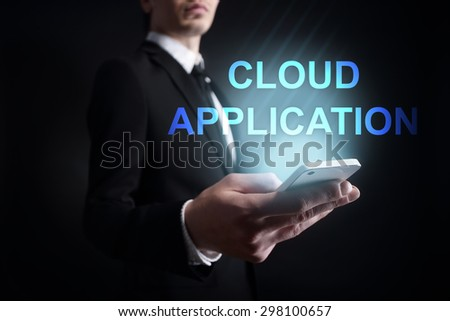 "Businessman holding a mobile phone with ""Cloud application"" text on virtual screen. Internet concept. Business concept. - stock photo"
