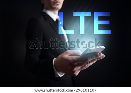 """Businessman holding a mobile phone with """"LTE"""" text on virtual screen. Internet concept. Business concept. - stock photo"""