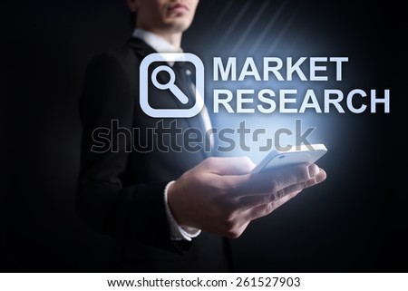 businessman holding a mobile phone with market research text on virtual screen. Internet concept. business concept. - stock photo