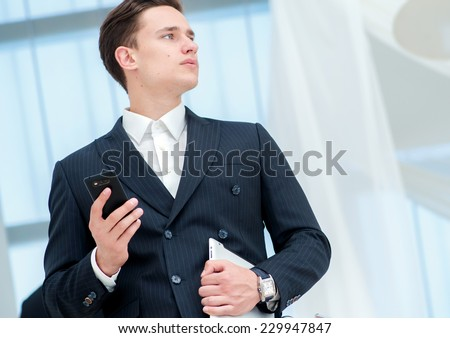 Businessman holding a mobile phone. Young businessman standing on the steps and keeps the tablet while it parnery talk to each other - stock photo