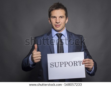 Businessman holding a paper that says support - stock photo