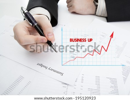 businessman holding a pen and counts the budget on the desktop - stock photo