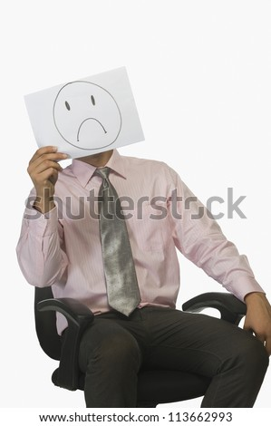 Businessman holding a piece of paper in front of his face with a sad on it - stock photo