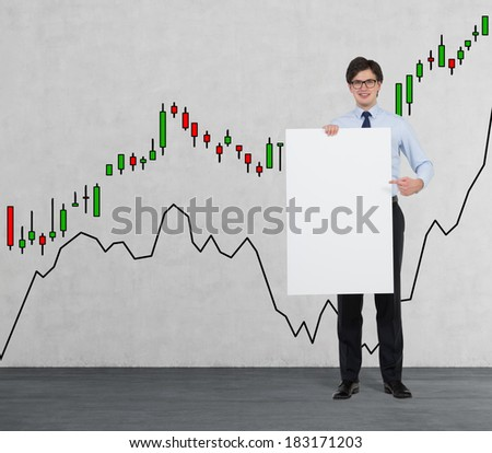 Businessman holding a placard. Charts wall background. - stock photo