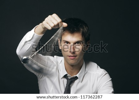 Businessman holding a pocket watch and swinging it in the fashion of a hypnotist - stock photo