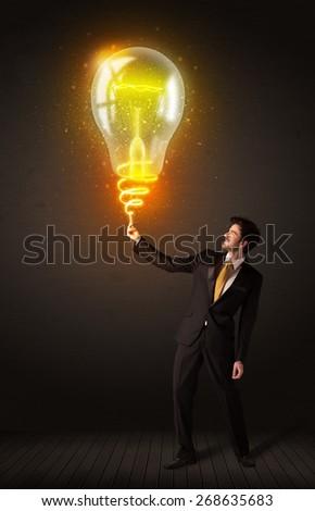 Businessman holding a shining idea bulb - stock photo