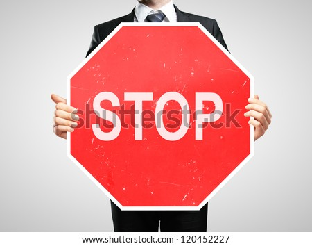businessman holding a stop sign - stock photo