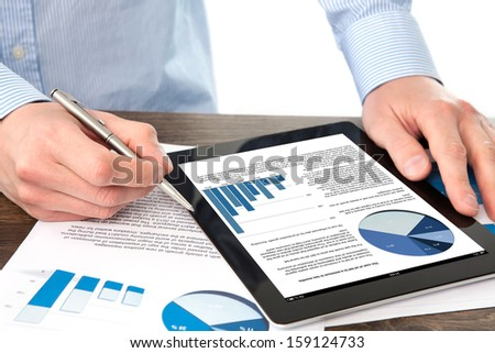 businessman holding a tablet computer with graphics on a screen on the table with documents - stock photo