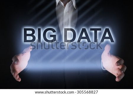 """Businessman holding a tablet pc with """"Big data"""" text on virtual screen. Business concept. Internet concept. - stock photo"""