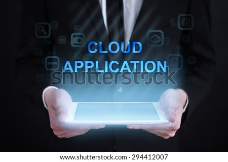 "Businessman holding a tablet pc with ""Cloud application"" text on virtual screen. Internet concept. Business concept. - stock photo"