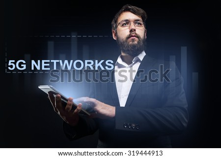 """Businessman holding a tablet pc with """"5G networks"""" text on virtual screen. Business concept. - stock photo"""