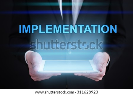 "Businessman holding a tablet pc with ""Implementation"" text on virtual screen. Internet concept. Business concept.  - stock photo"