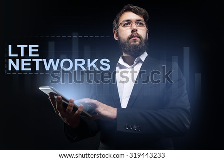 """Businessman holding a tablet pc with """"LTE networks"""" text on virtual screen. Business concept. - stock photo"""