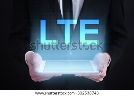 """Businessman holding a tablet pc with """"lte"""" text on virtual screen. Business concept. Internet concept. - stock photo"""