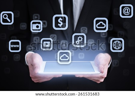 Businessman holding a tablet pc with mobile applications icons on virtual screen . Internet concept. business concept. - stock photo