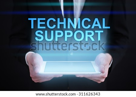 "Businessman holding a tablet pc with ""Technical support"" text on virtual screen. Internet concept. Business concept. - stock photo"
