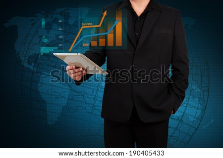 businessman holding a tablet showing business graph on virtual screen - stock photo
