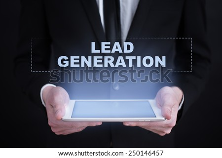 Businessman holding a tablet with a lead generation text. business concept. - stock photo